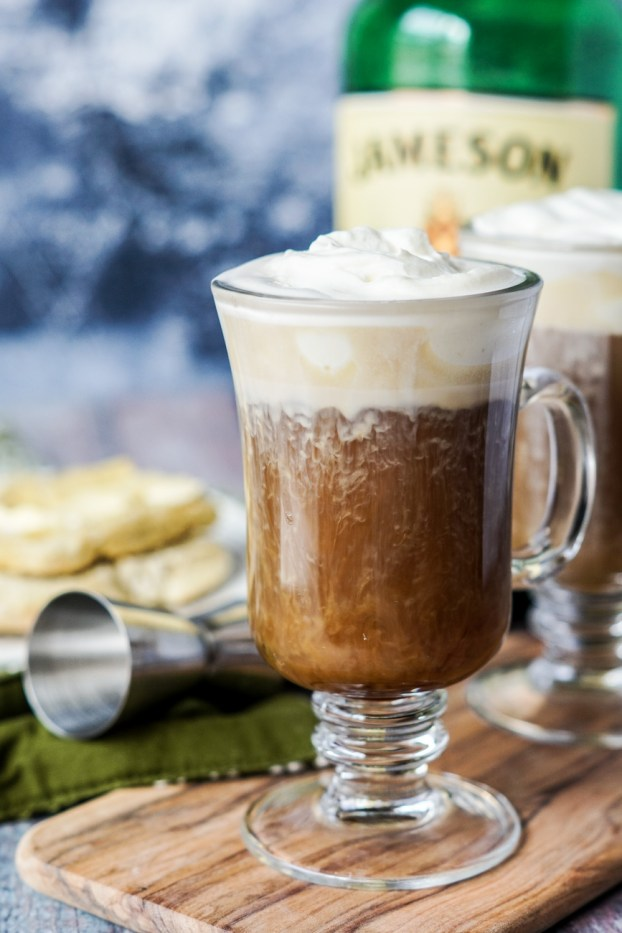 Side view of Irish Coffee in a tall glass mug with whipped cream.