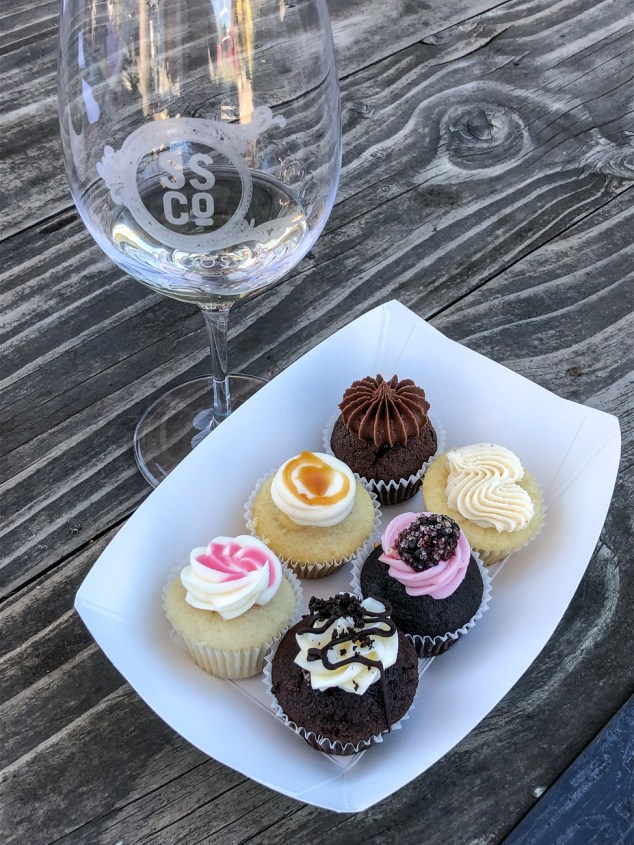Enjoy Cupcakes mini cupcake flight next to a glass of white wine.