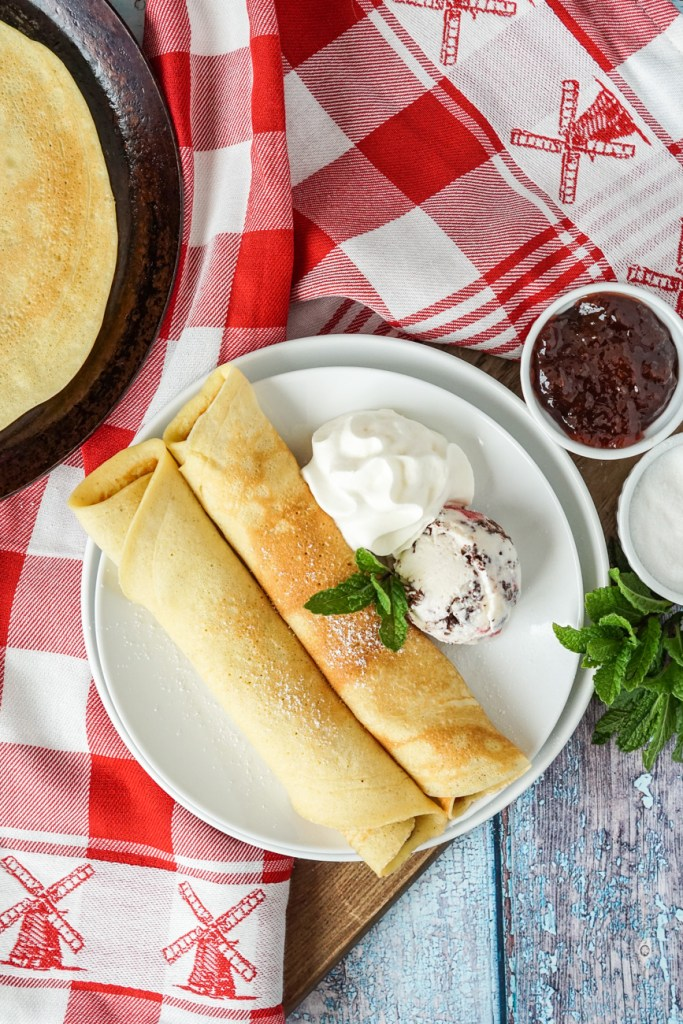 Pandekager (Danish Pancakes) with strawberry jam and ice cream on a white plate over a red and white towel with windmills.
