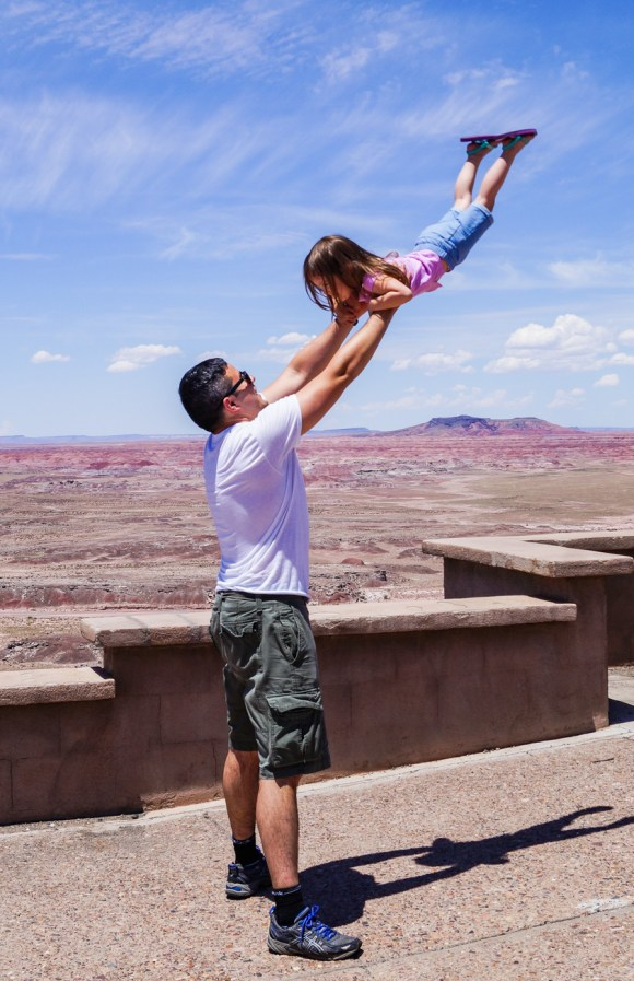 Father lifting daughter in front of Petrified Forest National Park