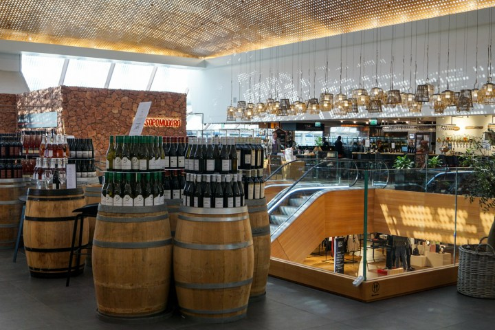 Top floor of ILLUM with wine bottles on barrels and lights