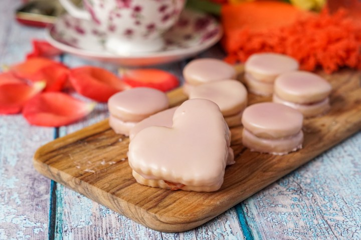 Heart and circular Napolitaines (Mauritian Sandwich Cookies) on a wooden board.
