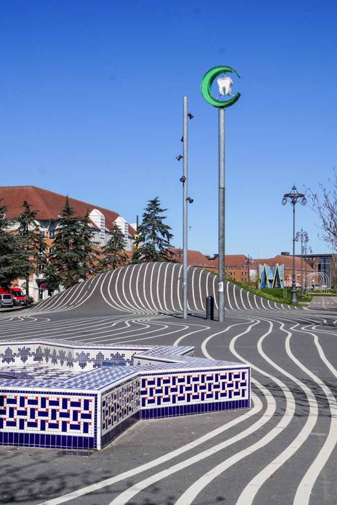 View of Superkilen- black pavement with white lines, a Moroccan fountain.