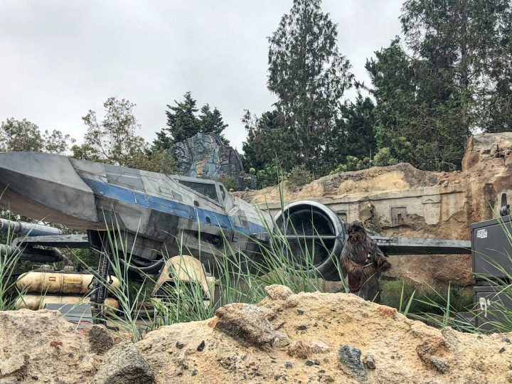 Chewbacca standing next to a grey and blue ship