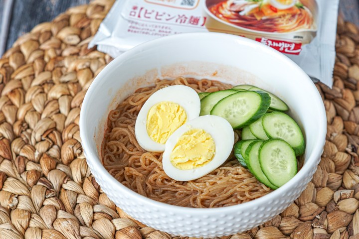 Fururu Cold Noodles topped with a halved hard-boiled egg and sliced cucumbers in a white bowl.