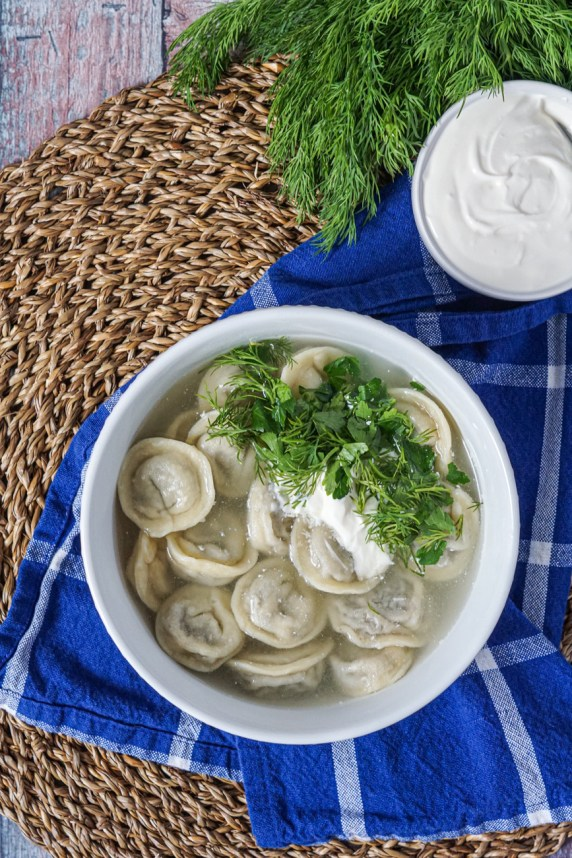 Siberian Pelmeni Dumplings in a broth with sour cream and fresh herbs.
