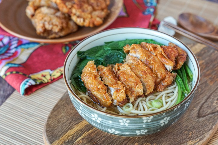Fried Chicken Soup Noodles in a bowl on a wooden board with more fried chicken in the background.