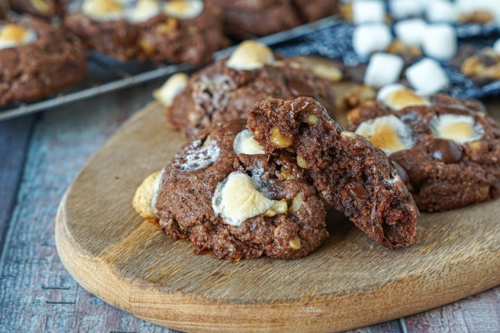 Inside of Rocky Road Cookies- chocolate cookies filled with walnuts, chocolate chips, and marshmallows on a wooden board