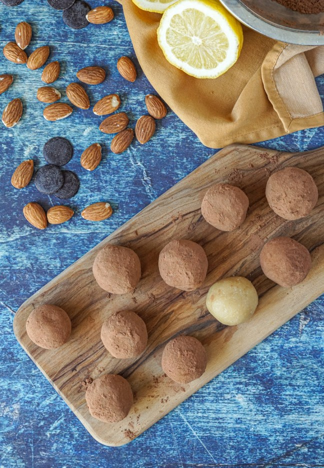 Aerial view of Badem Ezmesi (Bebek Almond Truffles) coated in cocoa powder on a wooden board next to almonds, chocolate chips, and a lemon half.