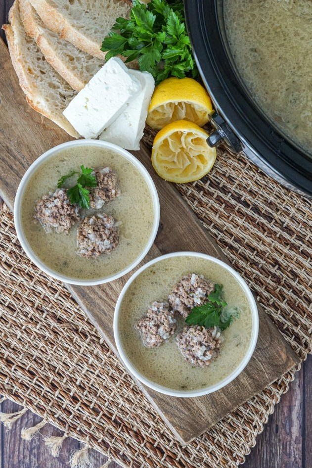 Aerial view of Giouvarlakia Soupa (Beef and Rice Meatballs in Egg-Lemon Soup) in two white bowls next to a slow cooker.