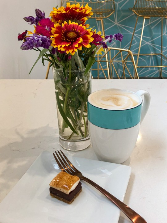 Salted Caramel Latte and Petite S'mores Bar next to a vase of yellow/orange and purple flowers at Bites & Bashes.