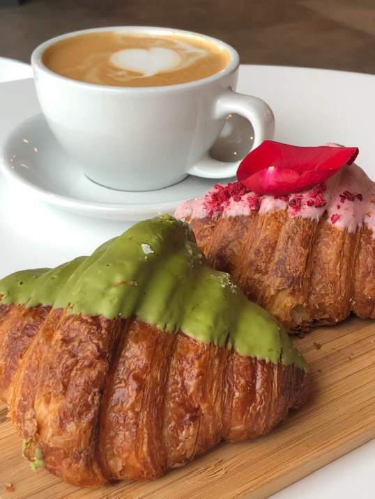 Two croissants (one matcha and the other rose) on a wooden board with a latte in the background in a white mug from Corridor Flow.