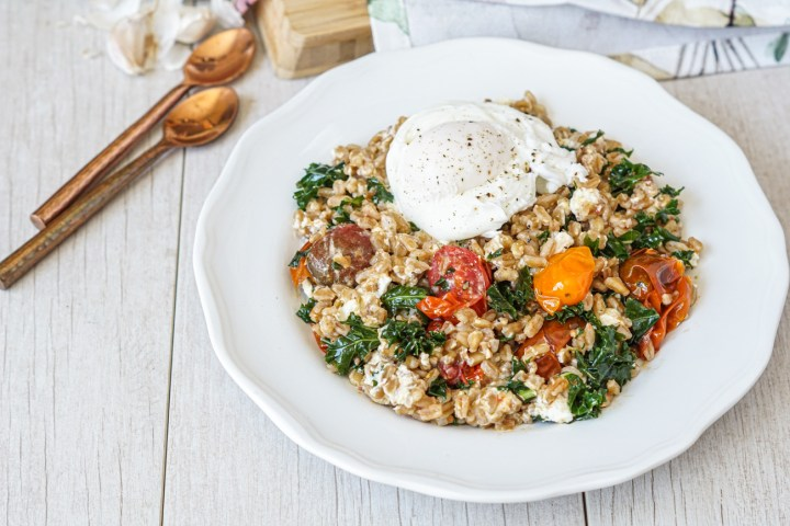Farro Salad with Kale and Roasted Tomatoes on a white plate next to two copper spoons.