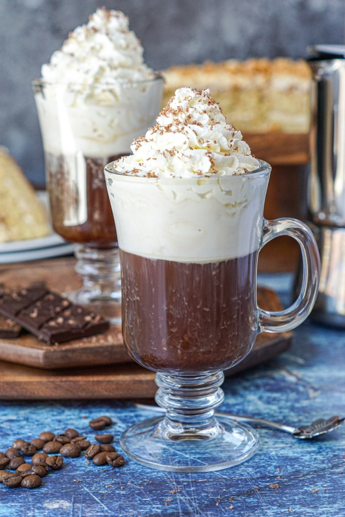 Einspänner (Viennese Coffee with Whipped Cream) in a tall glass with a handle next to coffee beans with another glass and a hazelnut cake in the background.