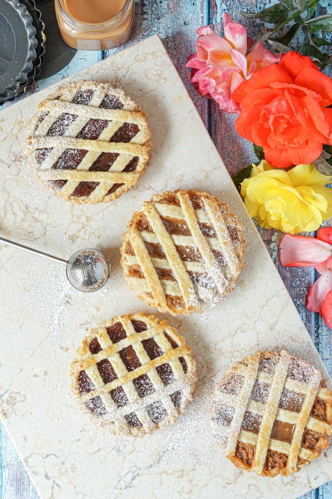 Aerial view of Pasta Frola (Argentinian Lattice Tart) on a marble board next to pink and yellow roses.