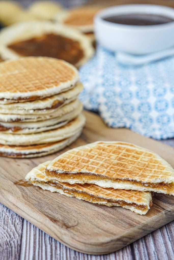 A stack of six Gaufres Fourrées (Little Sugar Waffles) with another one cut in half to show the creamy sugar filling.
