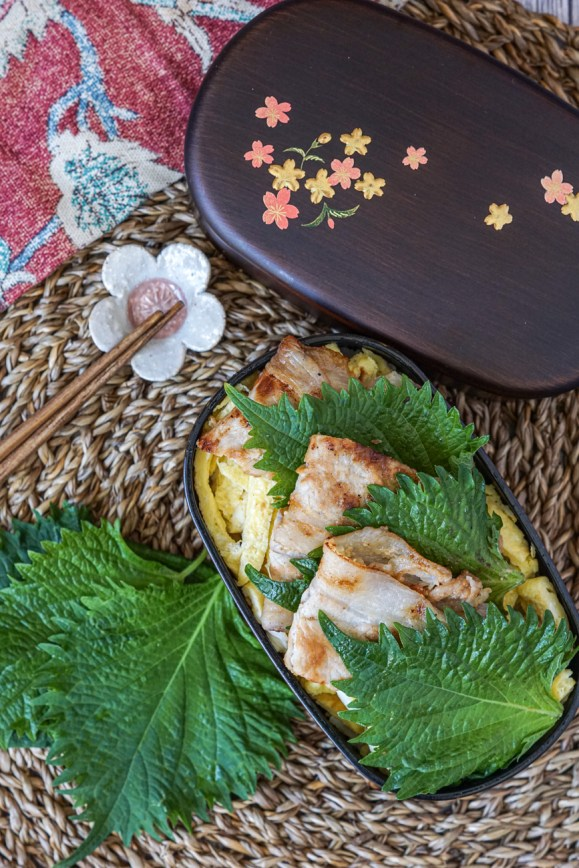 Aerial view of Miso Pork Rice-Bowl Bento in a dark wooden bento with pink and golden flowers next to wooden chopsticks on a cherry blossom chopstick rest.