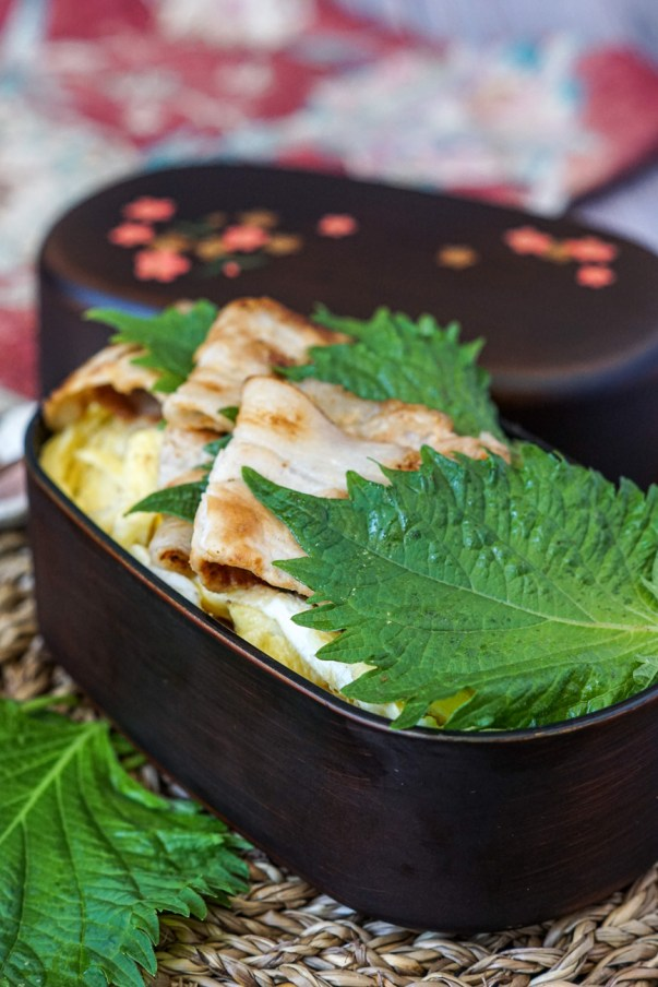 Miso Pork Rice-Bowl Bento with layers of thinly sliced pork and green shiso leaves in a dark wooden bento with pink flowers.