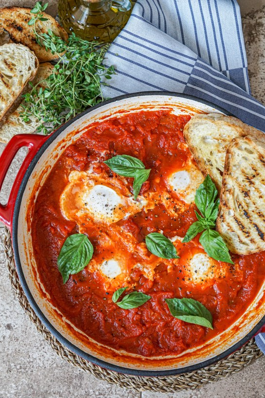 Aerial view of Poached Eggs in Italian-Style Tomato Sauce topped with fresh basil leaves and two slices of grilled bread in a red ceramic skillet. Next to the skillet is three more slices of grilled bread, a bunch of fresh thyme, a glass bottle of olive oil and a gray and white striped towel.
