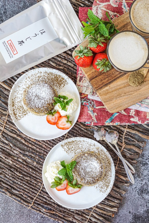 Aerial view of Hojicha Lava Cake on two white plates. Each has a dusting of Hojicha Powder, fresh mint, whipped cream, and strawberries. They are next to a silver bag of Hojicha Powder, three more fresh strawberries, fresh mint, and two glasses of hojicha latte.