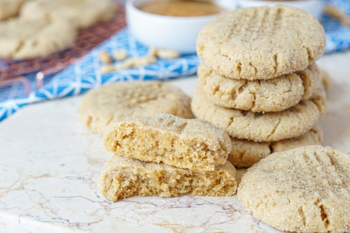 Four stacked Peanut Butter Cookies on a marble board next to two other cookies and a third in front cut in half and stacked to show the chewy texture.
