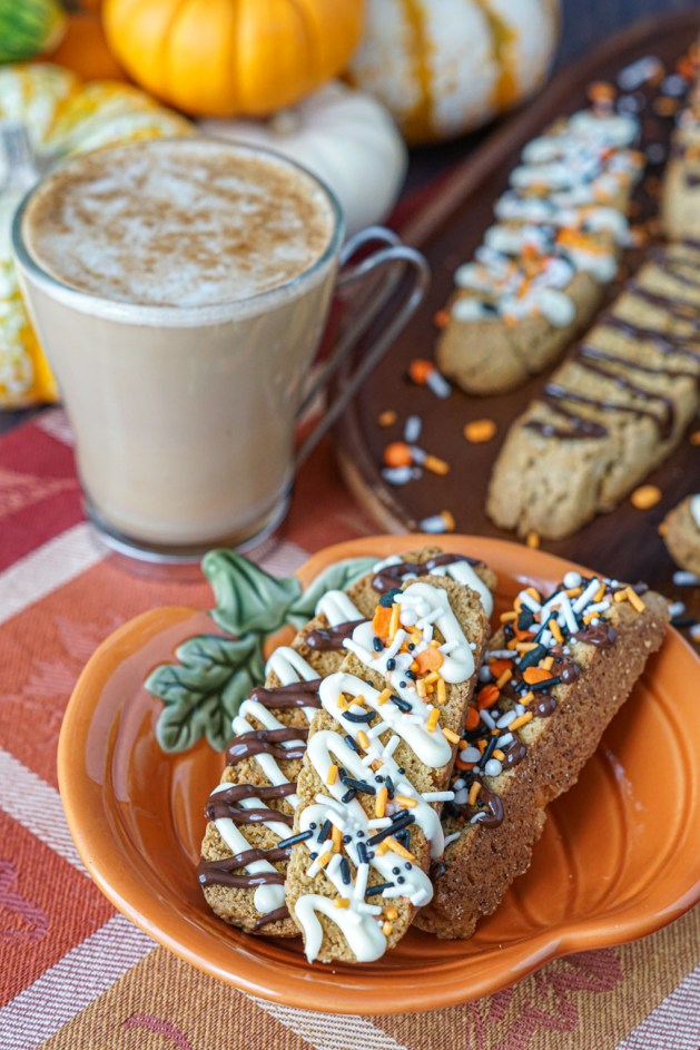 Three Pumpkin Spice Biscotti on a pumpkin plate next to more on a wooden platter and a latte.