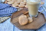 Three Biscotti Diamante on a wooden board next to a glass of coffee.
