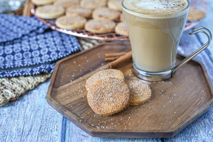 Three Biscotti Diamante on a wooden board with a glass of coffee.