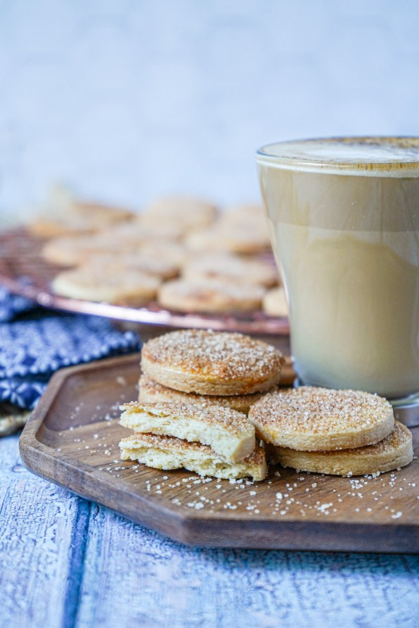 Side view of stacked Biscotti Diamante on a wooden board next to a glass of coffee.