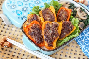 Blue bento box filled with Stuffed Bell Peppers, lettuce, mushrooms, and spinach.