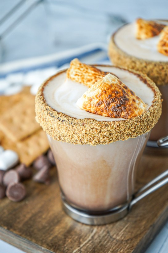 Side view of S'mores Latte in two glasses with graham cracker rims and toasted marshmallows on top.