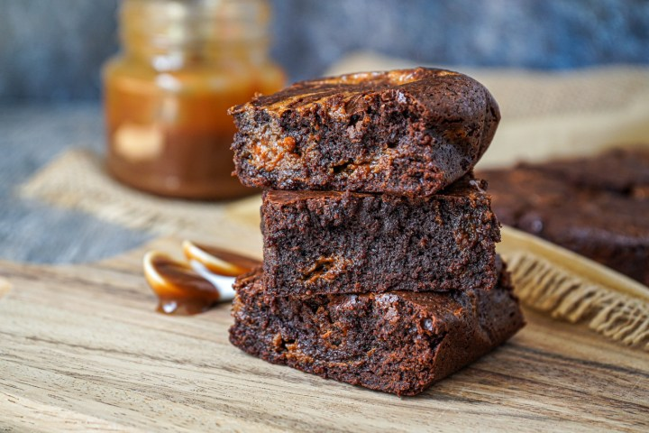 A stack of three Dulce de Leche Brownies on a wooden board.
