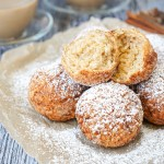 Louisiana Calas on a tan sheet of parchment with powdered sugar.
