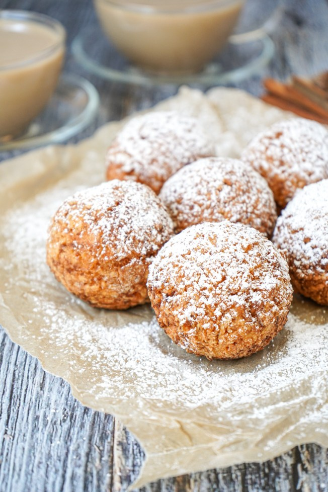 Six Louisiana Calas on a sheet of parchment and covered with powdered sugar.