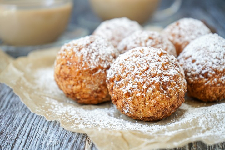Side view of six Louisiana Calas covered in powdered sugar.
