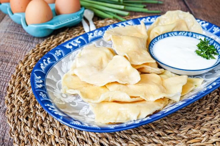 Tuxum Barak (Khorezm Egg Dumplings) on a blue and grey platter with a yogurt dip.