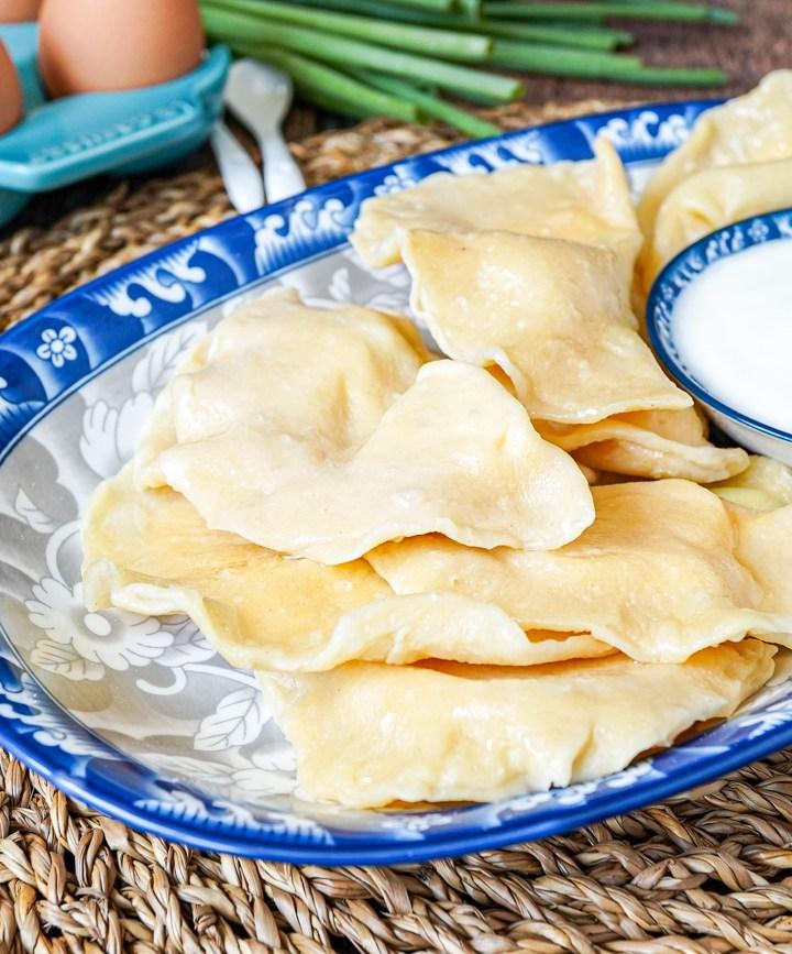 Tuxum Barak (Khorezm Egg Dumplings) on a blue platter next to yogurt dip.