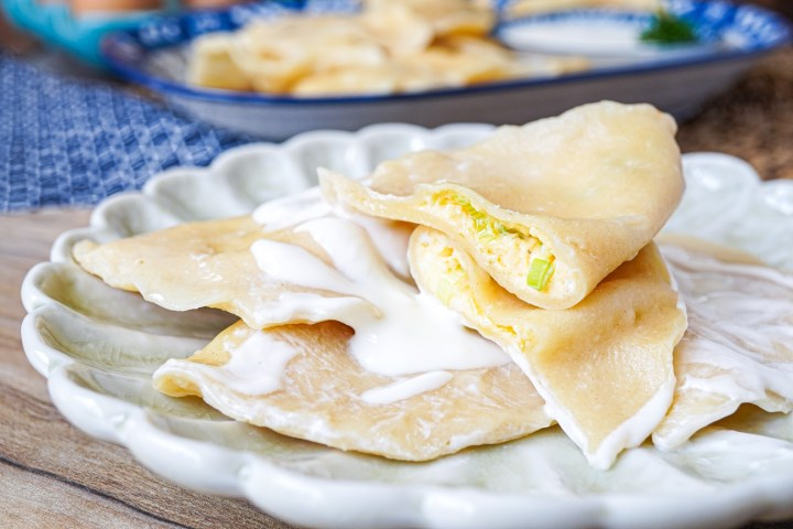 Close up of Tuxum Barak (Khorezm Egg Dumplings) with the top one cut in half to show egg filling.