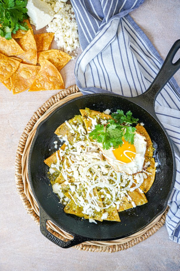 Aerial view of Chilaquiles Verdes in a cast iron skillet next to tortillas, cheese, and cilantro.
