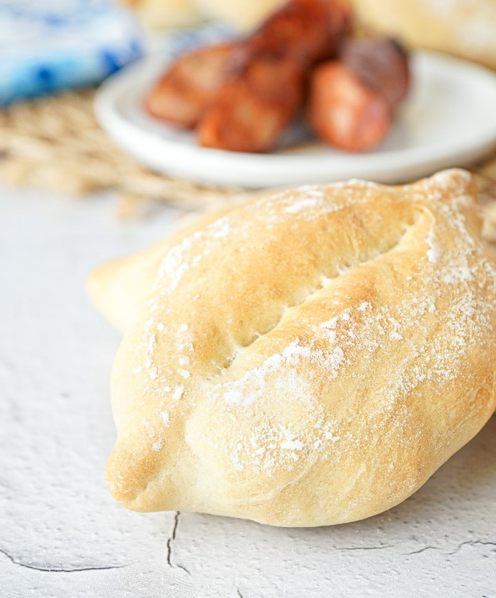 Papo Secos (Portuguese Crusty Rolls) with grilled sausage in the background.