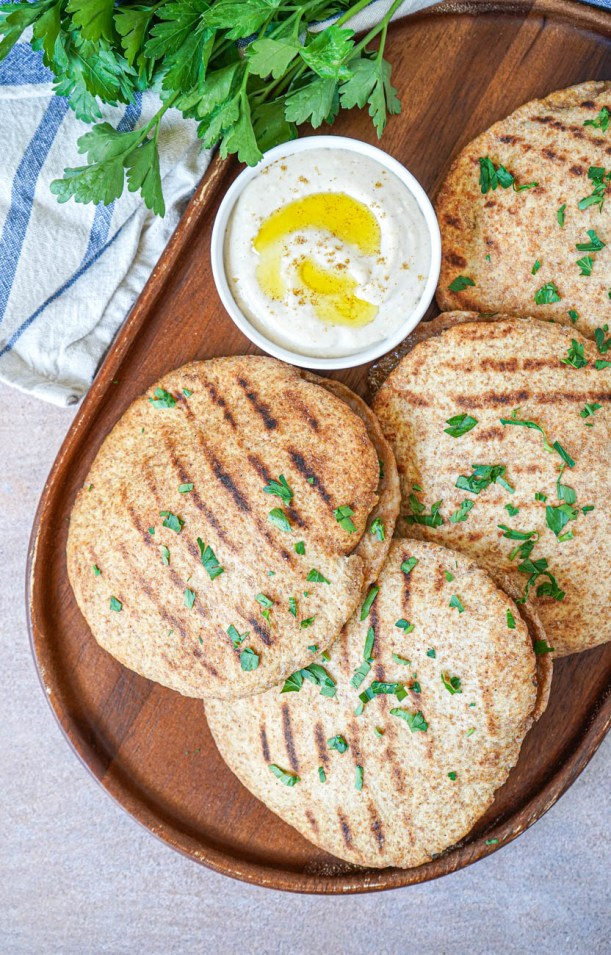 Aerial view of Hawawshi (Egyptian Meat Stuffed Bread) on a wooden board next to tahini dip and parsley.