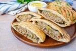 Hawawshi (Egyptian Meat Stuffed Bread) cut in half on a wooden board.
