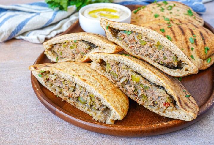 Halved Hawawshi (Egyptian Meat Stuffed Bread) on a wooden board.