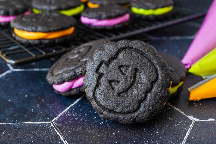 Homemade Chocolate Sandwich Cookies decorated for halloween with pumpkin stamp and orange, purple, green filling.