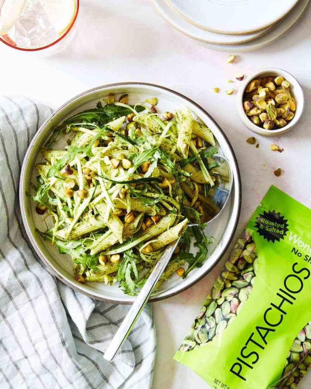 Bowl of pistachio pesto pasta with bag of green pistachios