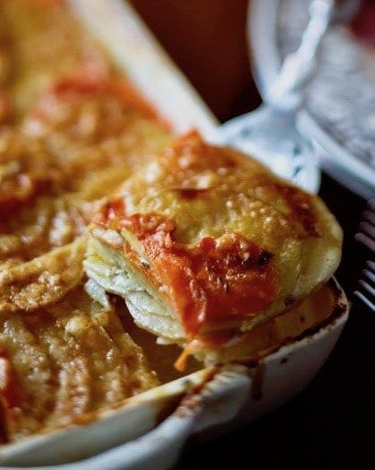 golden carrot and potato gratin in a dish cut square
