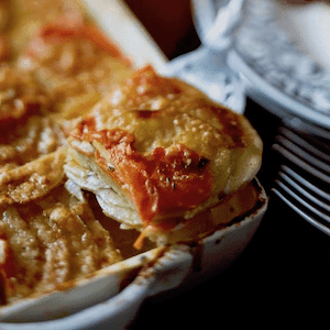golden carrot and potato gratin in a dish cut into a square