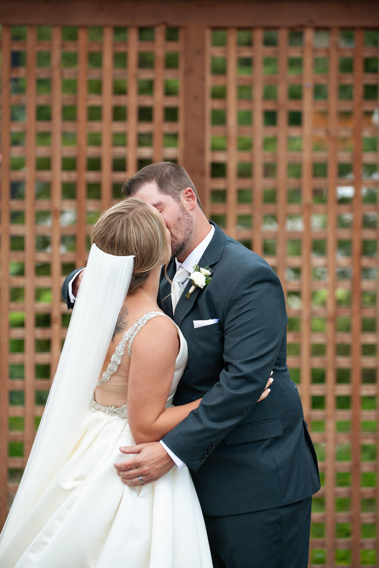 First kiss after a Creekside Villa wedding captured by Canmore wedding photographer Tara Whittaker