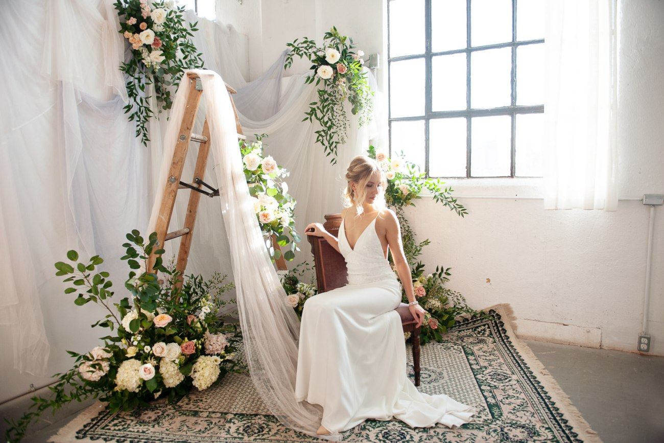 bride seated with flowers and vintage ladder captured by Tara Whittaker Photography