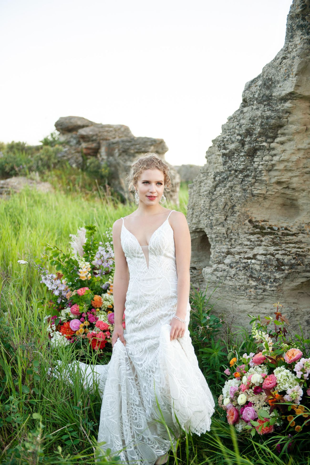 bride stands among her wedding flowers captured by Tara Whittaker Photography